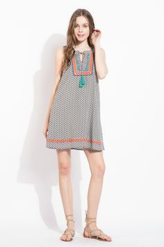 Love this bohemian print THML dress featuring a halter neck, orange and teal embroidery, and tassels! Great for spring.