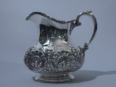 Sterling silver water jug. Made by Theodore B. Starr, C 1910. Squat and bulbous body, wide mouth and lip spout, foliate scroll handle, and circular foot. Repoussé flowers and shells on body. Applied scrollwork to rim. Foot unornamented. A pretty piece for use and display. Dimensions: Height: 7 ¾ in. Width: 4 in. Depth: 8 in. Weight: 27.5 Troy Ounces.