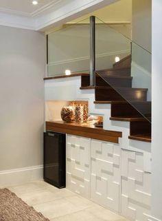 A arquiteta Silvana Lara aproveitou o espaço reduzido da sala para colocar a adega, um armário e também um aparador retrátil, que serve de apoio para a mesa de jantar no espaço embaixo da escada Foto: Divulgação