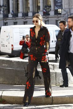 While out in Paris during PFW, Gigi wore black and red floral separates by Jenny Packham, accessorized with a Versace backpack.