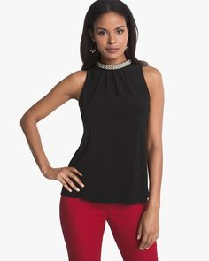 Faux pearl necklace around neck on black sleeveless top.