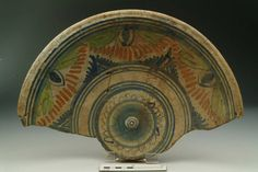 Accession number: 22719 Collection place: England or Netherlands 1571-1800 Earthenware H 75 mm; DM 375 mm Post-Medieval Half of English/Dutch tin-glazed ware plate. A fruit bowl shape, with a turned over lip. There is a stylised blue flower at the centre surrounded by three rings. On the sides are green fronds edged with blue, appearing from the top with large blue buds. Yellow dashes hang in swags around each pair of fronds above pyramids of blue. Three lines edge the design on each side.
