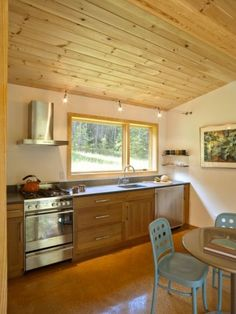 """A variety of different-size windows (from the economically priced Integrity window line by Marvin) capture light and the view. """"I wanted the windows to work from the exterior but relate to the interior space as well,"""" says Heaton"""