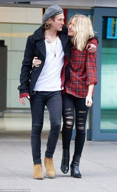 Back together: Ellie Goulding, 28, and her boyfriend Dougie Poynter, 27, were reunited at Heathrow airport on Sunday after a week apart