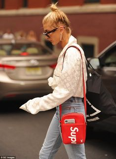 94eb1f3a2c9 Hailey Baldwin shows hint of midriff in tied up white shirt and jeans