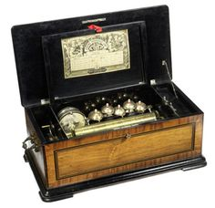 """A Jerome Thibourville Lamy """"Bells and Drum in Sight"""" cylinder musical box, Swiss, late 19th century, the 12 ½ in cylinder playing eight airs accompanied by five bells with wasp strikers and snare drum, in walnut veneered case with marquetry inlaid lid, 25in (64cm) wide"""