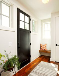 White walls, black door, corner wood bench, printed orange throw pillow, and striped grey rug