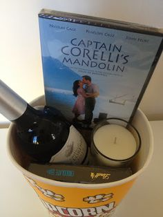 Romantic Movie Night idea (for a couple) Contains: Romantic film Gourmet popcorn Bottle of wine Small box of chocolates Scented candle - ooh-la-la!