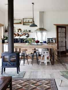 Kitchen with stools and wood stove.
