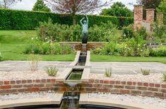 Garden water feature through a statue