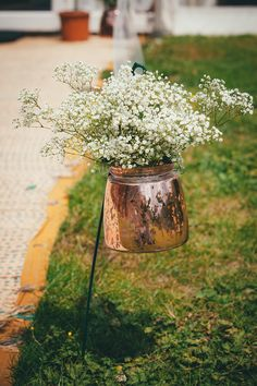 Copper kettle filled with gypsophila - Lucy G Photography - A marquee wedding with a lace gown and colour pop theme with mix and match centrepieces.