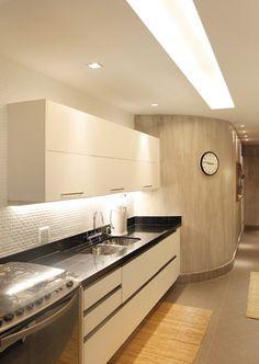 Iluminação na cozinha com rasgo iluminado, algumas lampadas espaçadas no corredor e próximas à pia. Foi utilizado também uma lâmpada tubular embutida no armário.