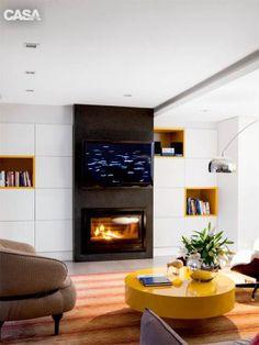 Na sala da lareira projetada pela arquiteta Pauline Fardo, o armário de MDF com pintura de poliéster e sem puxadores (Duocasa) ganha ares de painel e brinca com os nichos amarelos para objetos.