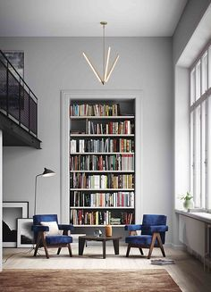 Have tall ceilings? Use your vertical space to create drama. Here, a tall bookshelf and nearly kinetic light fixture draw your eyes upward to show off the lofty feel of this living space.