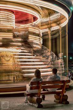 As time goes by in Paris, a couple waiting for their child enjoying a ride on the carousel. The long exposure gives the effect of time passing by.