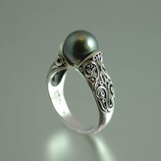 This breathtaking ring was designed and crafted by the artist and jewelry designer Sergey Zhiboedov. It is made of 14K white gold.    The ring is adorned with intricate lace-like floral carvings, and set a genuine 8.6mm Tahitian pearl. The ring shown on the photos is size 7. It can be custom made in any size from 5 to 9.5.    The white gold ring is shown with an antique tarnish (black rhodium plating), which adds sophistication and shows off the beautiful carvings. $1,375.00