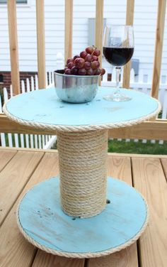 To make this side table, take an old electrical wire spool and wrap the center with jute rope. Then, paint it a beachy blue hue and distress it to make it look sea-weathered.
