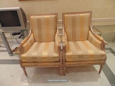 Lot 501 - A pair of Italian Neoclassical style antiqued distressed wood and parcel gilt upholstered Bergere,