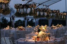 Wedding dinner tent with floral centerpiece and fully decorated chandeliers