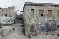 Aryz-2013-Barcelona  Aryz es uno de esos artistas contemporáneos que viajan de proyecto en proyecto por medio mundo. Su obra es reconocida por un uso especial del color. Empezó pintando por pura diversión en zonas poco transitadas, bajo puentes y vías de tren. En 2010 le invitaron a pintar una gran fachada en Italia, desde entonces su trabajo empezó a verse más.