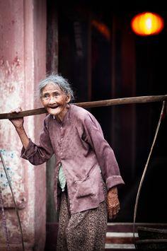 Anciana de la ciudad de Hoi An transportando mercancía de la forma tradicional Vietnamita.
