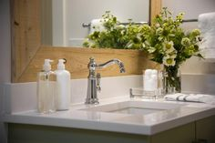 A polished chrome farmhouse-style faucet complements a white Silestone countertop, rustic wood mirror frame and a perky floral arrangement.