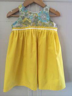 robe plissée taille haute en Liberty et popeline de coton jaune. Boutonnage total au dos avec boutons nacre; Ruban écru à la taille. taille 2ans.