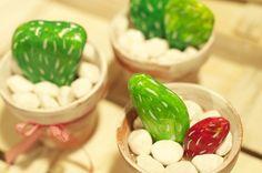 Sassi dipinti a mano per creare cactus in vasetti di coccio, decorati con nastrini di stoffa.