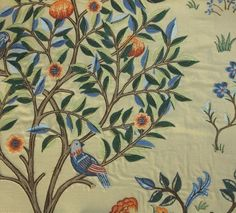 Kelmscott Tree Fabric Embroidered fabric of a tree design in greens and blue with russet and orange flowers and blue birds, on a sagey taupe cloth