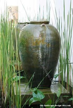 large clay pot fountain in a pond