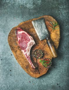 #Dry aged raw beef rib eye steak  Dry aged raw beef rib eye steak with bone butcher meat chopping knife and spices in bowls on rustic wooden board over grey concrete background top view