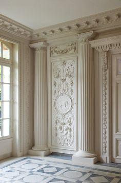 Un estilo clásico con yeso. Me agradan bastante los detalles decorativos en la puerta y en el muro.