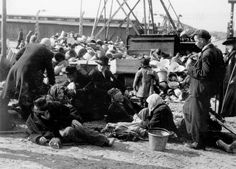 Birkenau, Poland, Deported Jews who are physically weak sitting next to confiscate​d possession​s, May 1944.