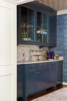 Blue wet bar boasts blue glass front cabinet suspended over blue lower cabinets adorned with brass knobs and pulls paired with gray and white marble countertops fitted with a round bar sink and gooseneck faucet as well as a gray and white marble slab backsplash.