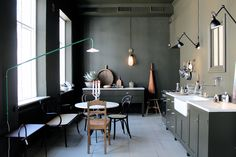 Gothenburg design shop Artilleriet created a shoppable apartment with kitchen featuring mismatched dining chairs, army green cabinets, and a pair of Lampe Gras wall-mounted lights. See more in Master Mix: A Shoppable Apartment in Gothenburg, Sweden. Photograph by Johanna Bradford courtesy of Artilleriet.