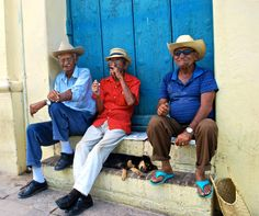 Three older men sitting on a stoop enjoying some cigars while a dog slept under them.