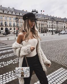 White sleeveless top, chunky sweater, and black pants.