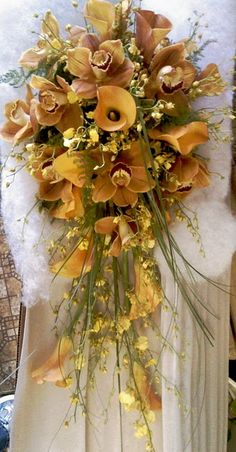 Elegant Lady. Beautiful cascading bouquet of Golden Tones in Miniature Calla Lilies, Cymbidium Orchids, Miniature Orchids and Bear Grass