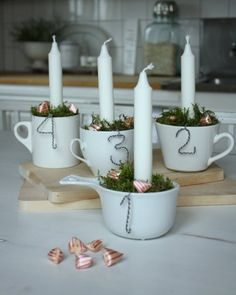 Advent candles - one is lit for every week in December. This mug theme is very cozy for the kitchen. The addition of red striped pocket pillow candies and green moss are just the right details with this mostly white decor.