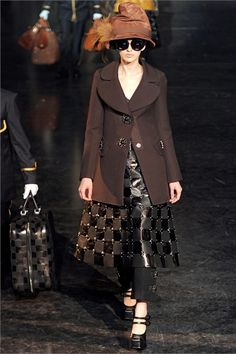 Louis Vuitton - Collections Fall Winter 2012-13 - Shows - Vogue.it. Plume hat. Outer coat that is worn over an A line skirt and a straight leg pants or breeches. Shoes are similar to a clog.
