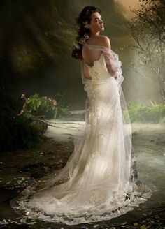 Ivory Tulle strapless Alencon Lace bridal gown, jeweled appliqué at empire waist, cascading handmade silk flowers at back, modified chapel train.