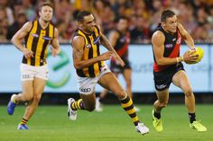 Orazio Fantasia of the Bombers runs with the ball away from Shaun Burgoyne of the Hawks during the round one AFL match between the Essendon Bombers and the Hawthorn Hawks at Melbourne Cricket Ground on March 25, 2017 in Melbourne, Australia.