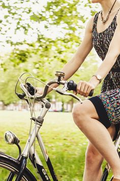 Person Wearing Black and Gray Sleeveless Dress Riding a Step Through Bicycle