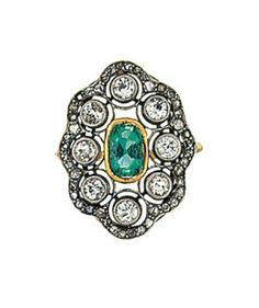 An emerald and diamond ring The oval-cut emerald collet within an openwork cartouche millegrain-set with old brilliant-cut diamonds to the rose-cut diamond frame