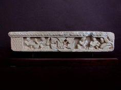 ART GRECO-BOUDDHIQUE DU GANDHARA (Ier - Vème siècle ap. J.C.)  Frise représentant des génies tenant une guirlande. Décors de tête de lion, oiseaux et fleurs. En schiste gris bleu. H : 8 cm L : 22 cm
