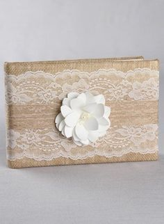 This stunning rustic wedding guest book is covered in burlap fabric with a delicate lace cover embellished with jute ribbon and satin flower with beaded centre.