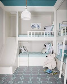 Aqua blue shared girl and boys bedroom features two sets of built-in bunk beds dressed in aqua bedding and pillows illuminated by black and white wall sconces. Bunk Bed With Slide, Bunk Beds With Stairs, Kids Bunk Beds, Bed Slide, Small Room Bedroom, Trendy Bedroom, Kids Bedroom, Bedroom Decor, Small Rooms