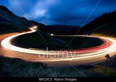 Car headlights trailing around a hairpin bend on a mounatin pass in South Wales. © Robin Funffinger / Alamy