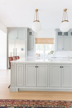 The kitchen is a study in neutrals. Leather stools by Dust and brass light fixtures from Rejuvenation bring warmth to the space | archdigest.com