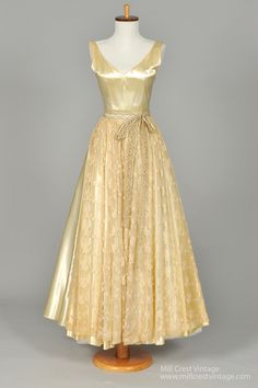 Designed in the 40's, this amazing vintage wedding gown is done in a glorious french vanilla slipper silk satin with an attached lace embroidered net, with a floral and bow pattern. The sleeveless bod
